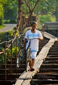 Carrying a bicycle with hands is more likely the safest way to cross the bridge.